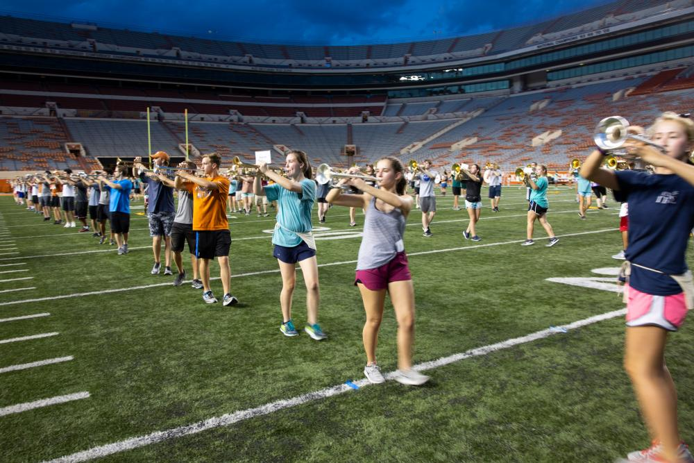 Longhorn marching band rehearsing on a football field