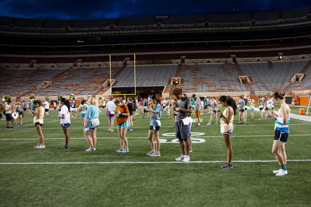 UT Longhorn Band members rehearsing on a football field