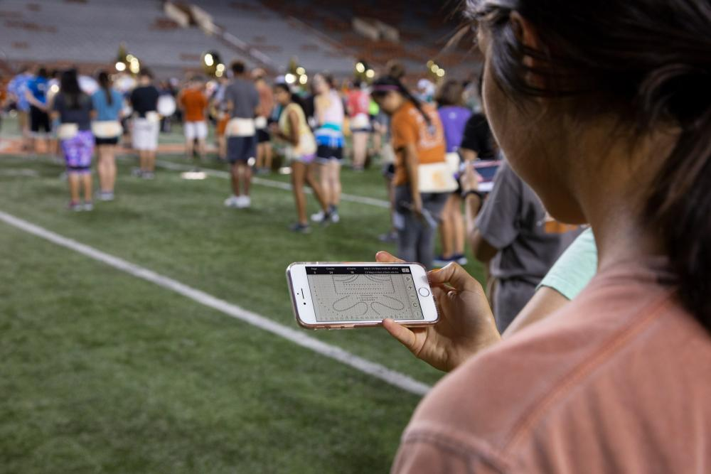 A UT Longhorn band member checks her phone for drill instructions