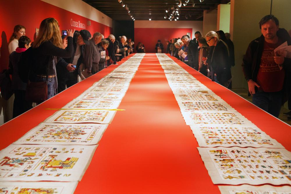 People gather in an art gallery to view hand-painted squares of paper that replicate the Codex Borgia
