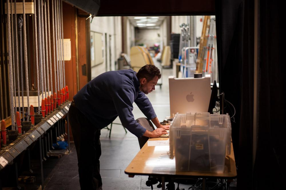 J.E. Johnson working at a computer backstage