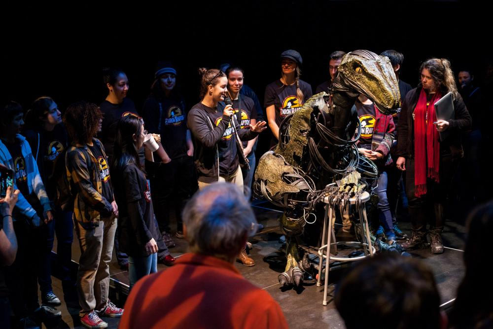 Students wearing Enron raptor tshirts at an unveiling with an animatronic raptor