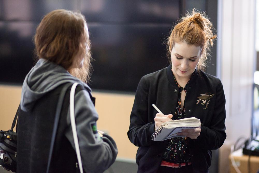 Felicia Day signing an autograph for a student