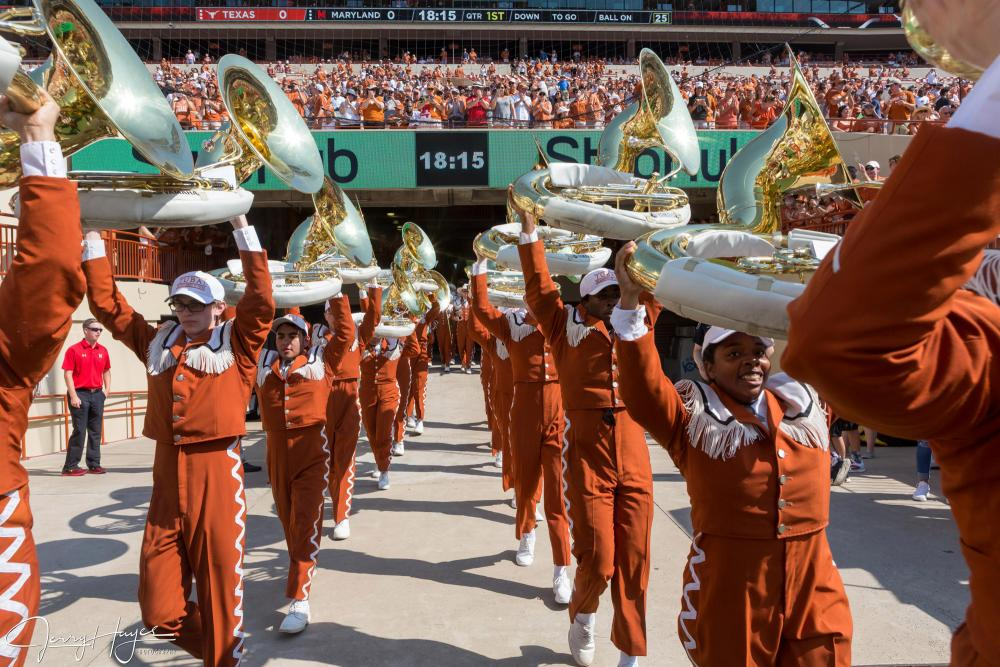 UT Longhorn band members holding their instruments above their heads and marching out to the football field