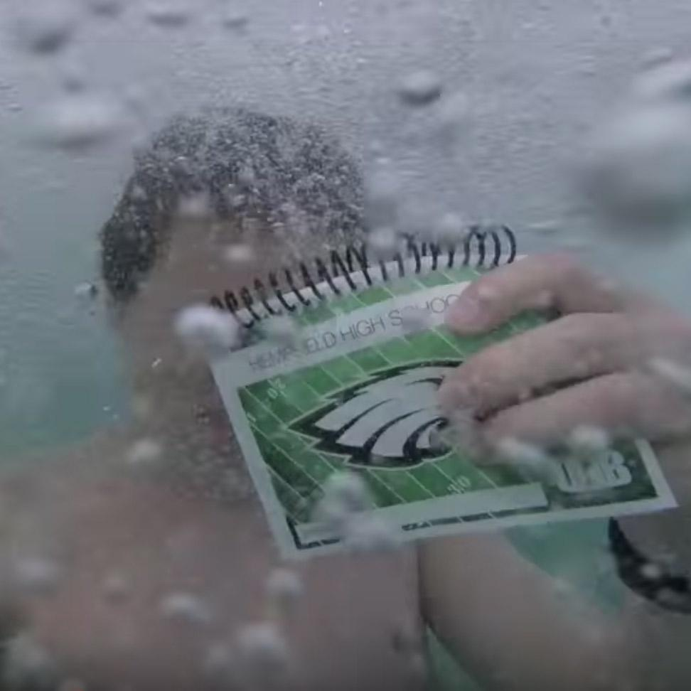 Luke Gall underwater with a drill book to show it's waterproof