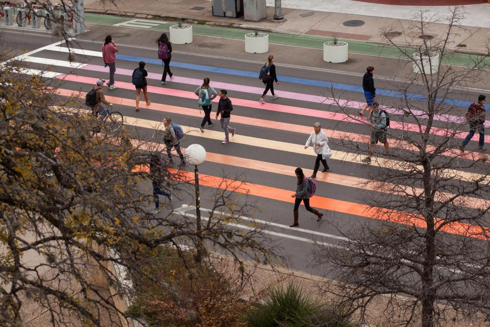An image of a crosswalk painted a rainbow of colors chosen from the palette of a sunset