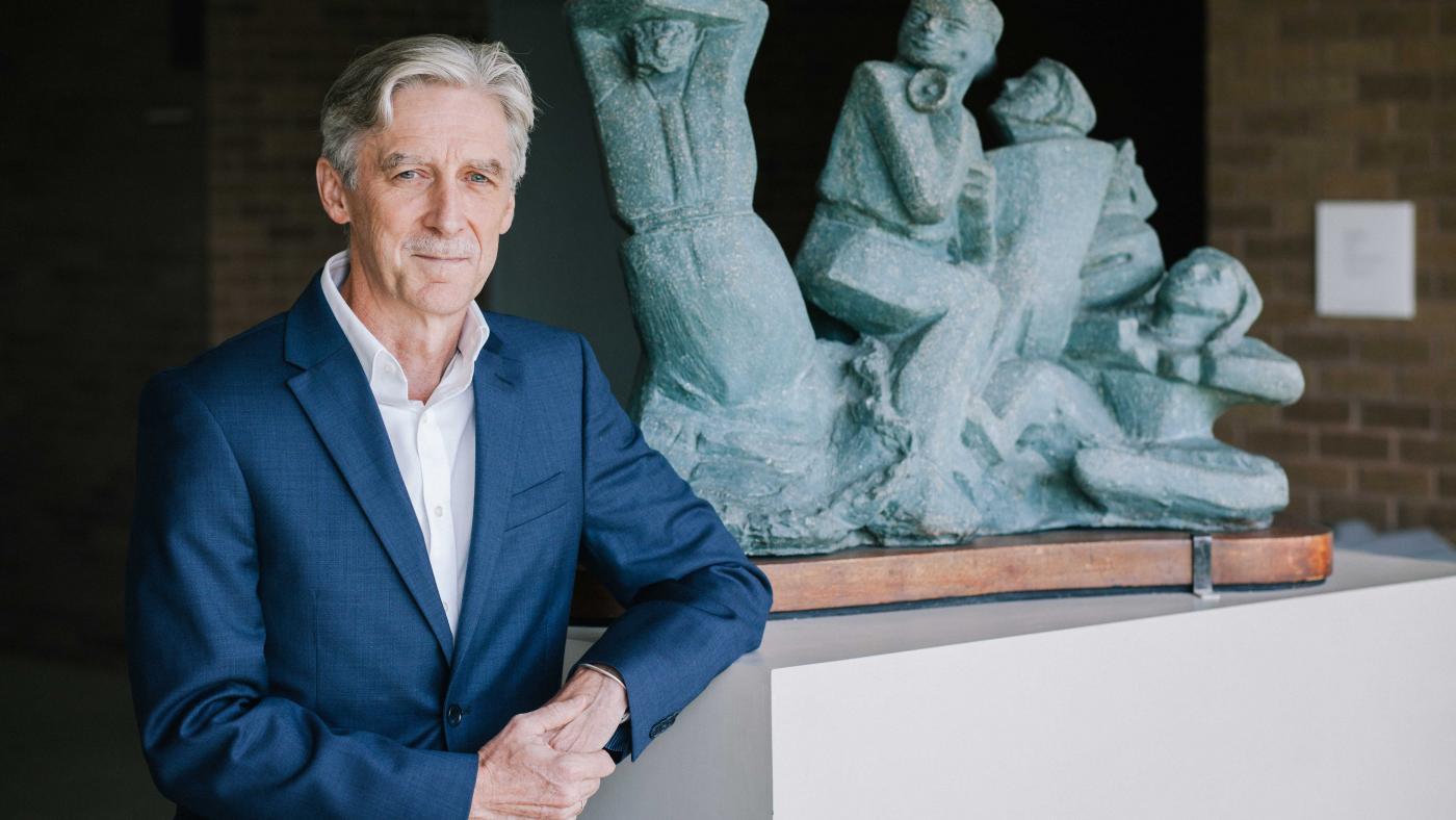 Dean Dempster standing next to Victory Ball sculptures by Anita Weschler