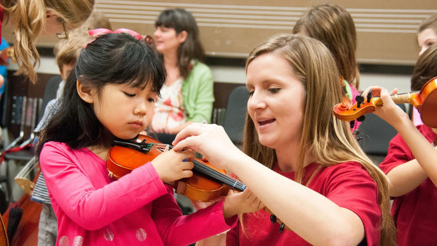 A UTeach Music student works with a young student on violin.