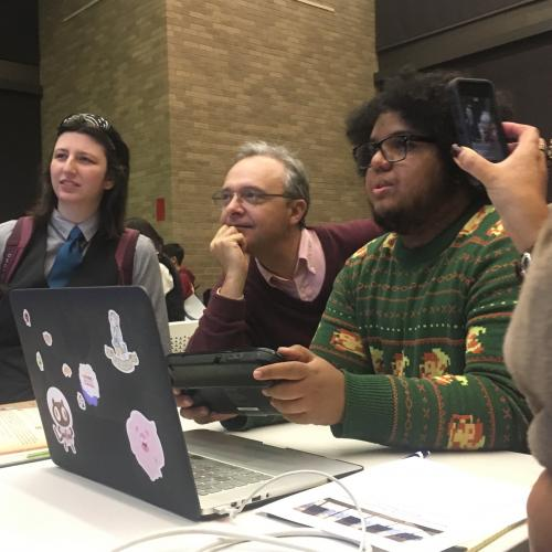 Joseph Ovalle points to a computer while people look at the screen