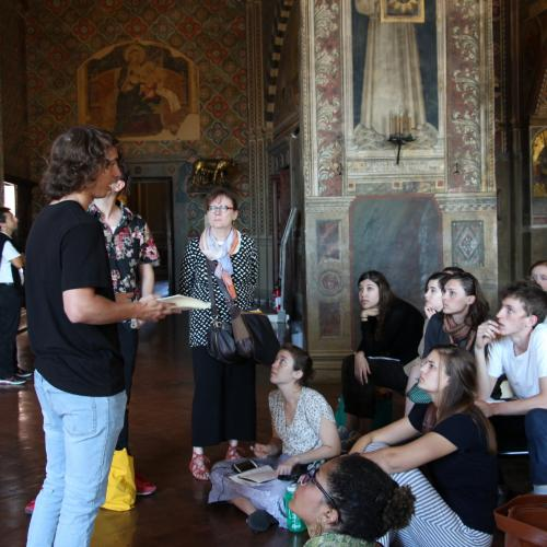 Ann Johns, far left, listens to Nick Purgett, an Art History sophomore, present at the Sala del Mappamondo in the Palazzo Pubblico in Siena.