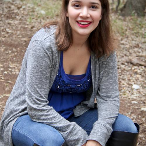 Laura Gonzalez sits in a wooded area
