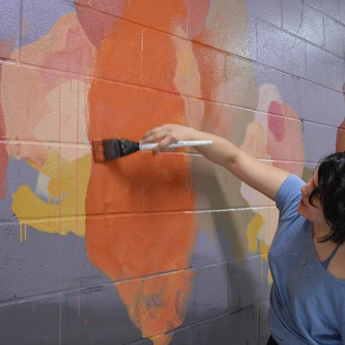 Victoria paints a mural on a wall in the Butler School of Music