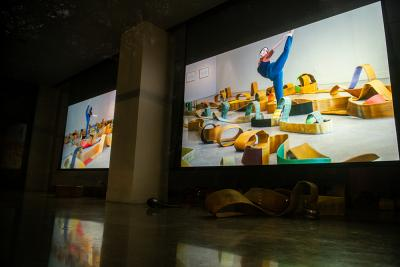 A projected screen shows a dancer moving through old firehoses on the art gallery floor.