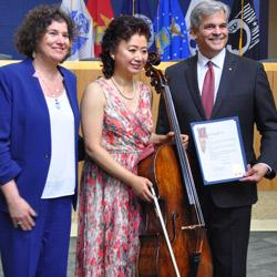 Hai Zheng with her cello and accompanied by Austin Mayor Steve Adler and city council member