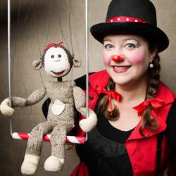 Honey Goodenough in clown make up with a sock puppet