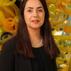 Roja Najafi stands in front of a work of art