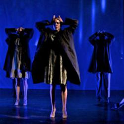 Jacqueline Heard Hinton on a blue-lit stage with other dancers