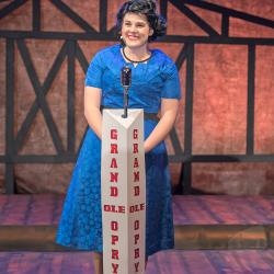Lilly Lane Stafford stands on a stage at a microphone dressed as Patsy Cline.