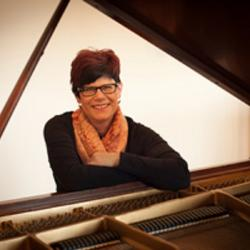 Lucia Unrau sits at a piano