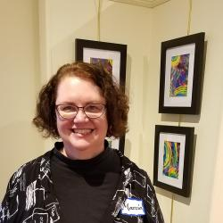 Marcia standing in front of three pieces of art hanging on a wall