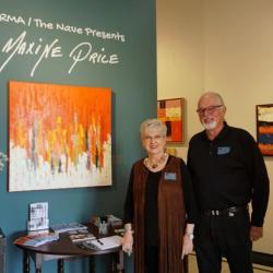 Maxine poses for a photo in front of her painting