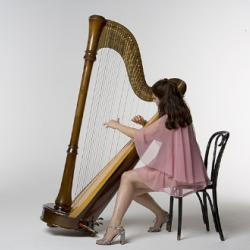 Mia Theodoratus wears a pink dress and plays the harp