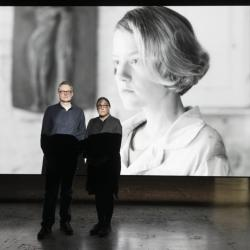 Andrew Birchler and Teresa Hubbard stand in front of their video work on a screen