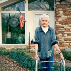 a photo of a woman with a walker in front of a house with a U.S. flag