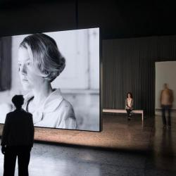 people in front of a large screen with a black and white film