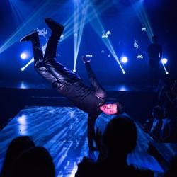 An image of a man doing a one-armed handstand with blue lights and lasers behind him