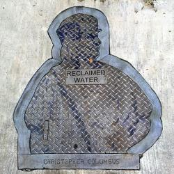 a street drain with the profile of a man and the words Christopher Columbus