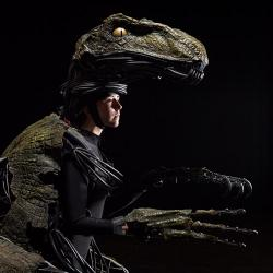 a woman wears an animatronic raptor suit. Her face is showing and she is looking off to the side. The background is black and the lighting is dramatic