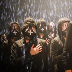 an image from the dance performance (Re)current Unrest where people are wearing dark cloaks with white crosses on the face masks