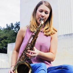 Sarah Millgan, with blonde hair and wearing a pink shirt, playing the saxophone outside