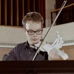 Sean Riley playing a 3D printed violin, which has a traditional violin neck but does not have the round hollowed body typical of violins