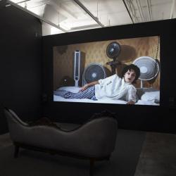 an art installation in a room with a couch and a film screen showing a woman laying on a couch