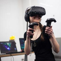 a woman wears a virtual reality headset at the AET showcase