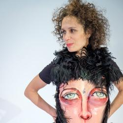 Yuliya Lanina, wearing a tshirt with a painted face on it and black feathers.