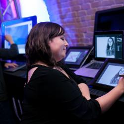 A student draws on a tablet at the launch exhibition for the Center for Arts and Entertainment Technologies. Photo by Lawrence Peart.