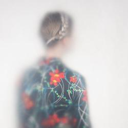 The back of a woman wearing a flowery shirt and braids in her hair.