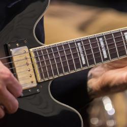 A hand strums a guitar