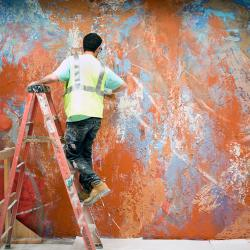 An image of Jose Parla on a ladder, wearing a hard hat and yellow construction vest while painting an abstract painting in a range of textured ambers, oranges, blues and grays