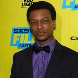 J Quinton Johnson stands in front a promotional background on the red carpet