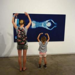 an adult and child look at art on the wall while holding their hands in the air