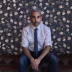 Michael Wellen sits in front of a floral wall