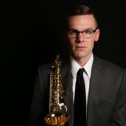 Nathan Mertens holds a saxophone