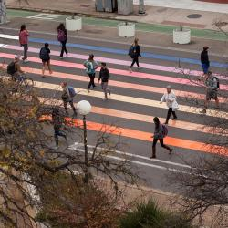 a birds-eye-view photo of students walking through the Sunset Crosswalk, painted the colors of a sunset