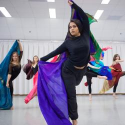Sofia performs dance moves while holding an Indian scarf