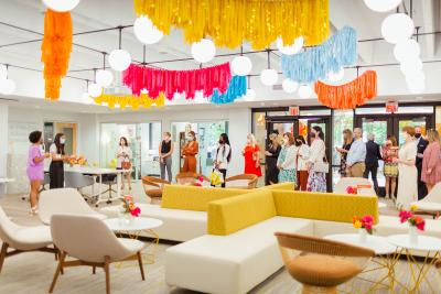 A group of mostly women, wearing masks, gathers inside a space decorated with bright colors and natural light