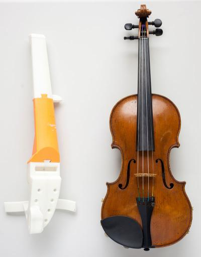 A 3D printed violin sits next to a traditional violin.
